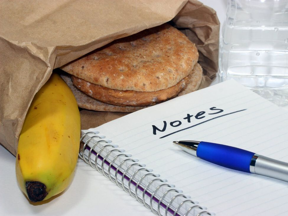 photograph of a lunch bag with a banana and sandwich